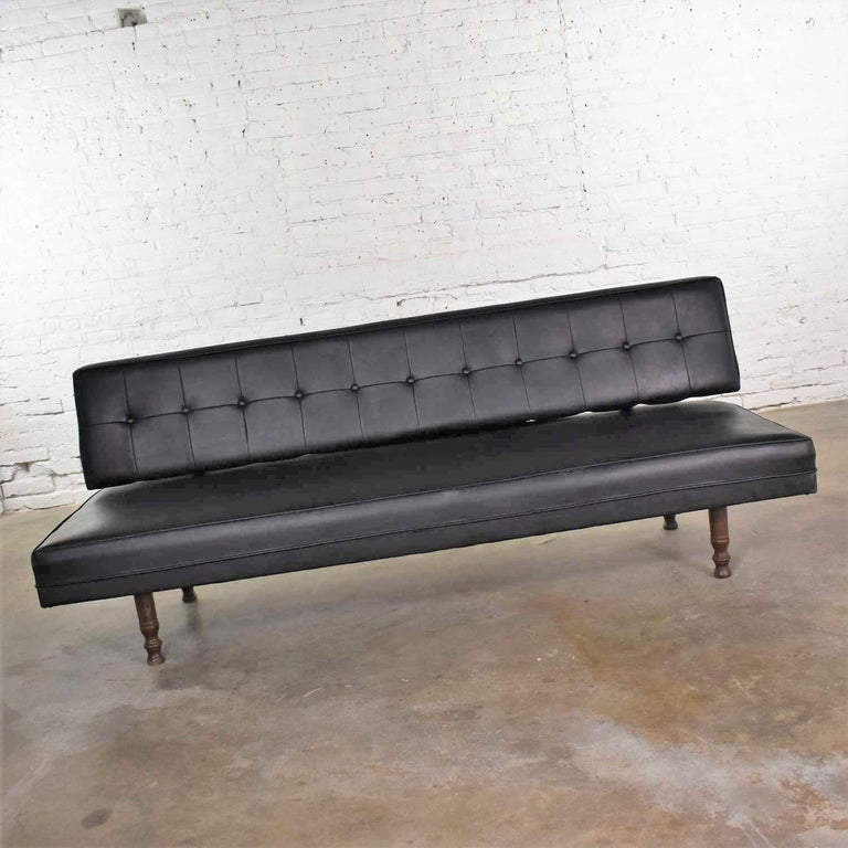 Handsome Mid-Century Modern settee or loveseat sofa in black vinyl faux leather by Universal of High Point. It is in wonderful vintage condition. We have restored the wood, cleaned the vinyl, repaired a few spots where stitching was loose, and put