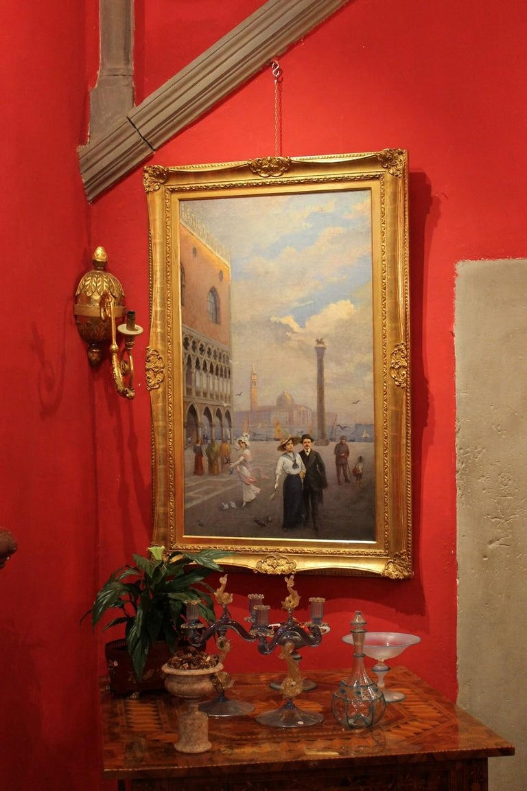 This delightful turn of the century (early 20th century) oil on canvas painting represents an Italian landscape with one of the most famous squares in the world: Piazza San Marco in Venice. The rectangular canvas paints the square from an unusual