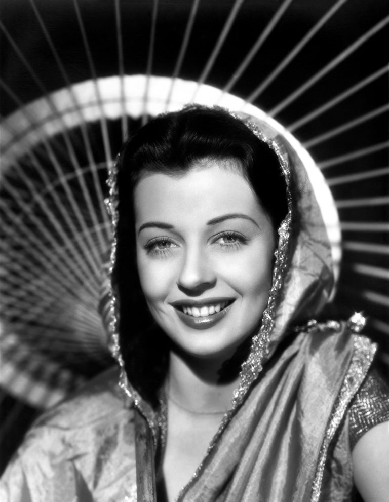This stunning studio portrait features Gail Russell, an American film and television actress, posed smiling in a shawl. Because of her ethereal beauty, Gail was to be groomed to be one of Paramount's top stars.   This image is credited to Globe