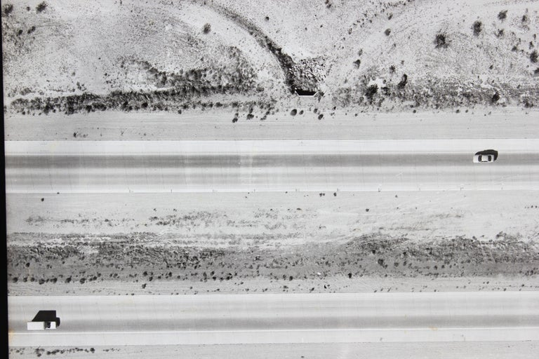 Photograph of a freeway with vehicles traveling on it. Has numbers and lines along the freeway making it look like a land surveyor's photograph. Photographer and time period taken is unknown.