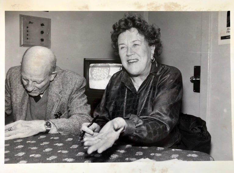 Julia Child. I believe that is her husband in the photo with her. This is a vintage photo from a newspaper archive. Julia Childs makes cooking cooking fun and easy... side profile photo black & white  portrait. Julia Carolyn Child was an American