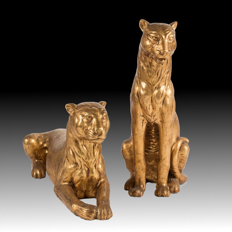 Pair of large lioness terracotta, fully gilded, one lying, the other sitting. Superb decorative value.  Italian manufacture Art Deco period, 1930s Golden terracotta with gold leaf  Measurements: cm 52 x 38 x h. 94 cm 99 x 42 x h. 49  Excellent