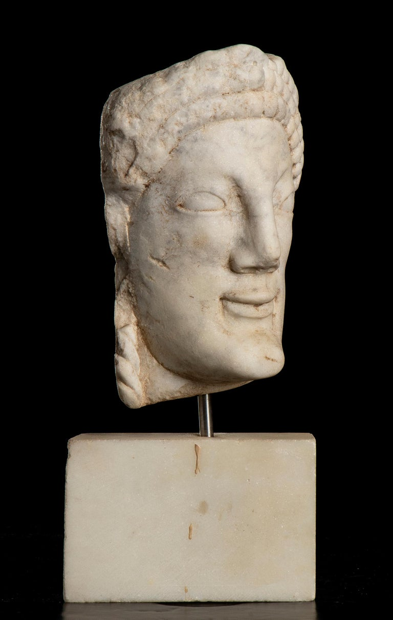 an iconic portrait of Kore, made in an Italian statuary white marble probably Rome after 1950. Kore is the modern term given to a type of ancient Greek sculpture of the Archaic period depicting female figures, always of a young age. Kouroi are the