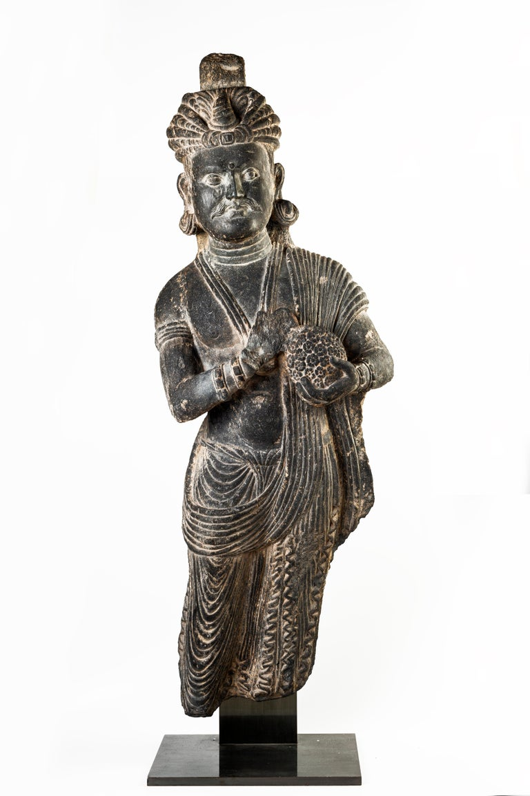 Gandhara Sculpture is a large gray schist statue representing a figure of a devotee with turbant..   From the drapery and the cloth sculptures, we could understand it deals with a statue from the Gandhara area, realized between the second and the