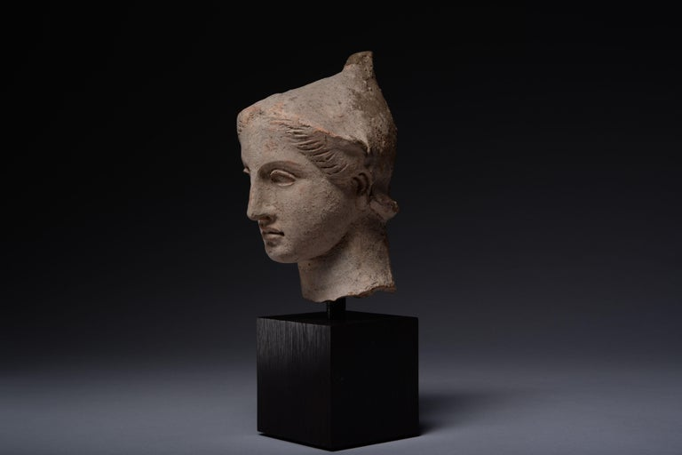 This delicate terracotta head is a magnificent example of Classical Greek art from Tarentum, modern-day Apulia. It depicts a youth with sensuously modelled lips and heavy-lidded, almond-shaped eyes. A peaked pilos helmet covers his short hair, which