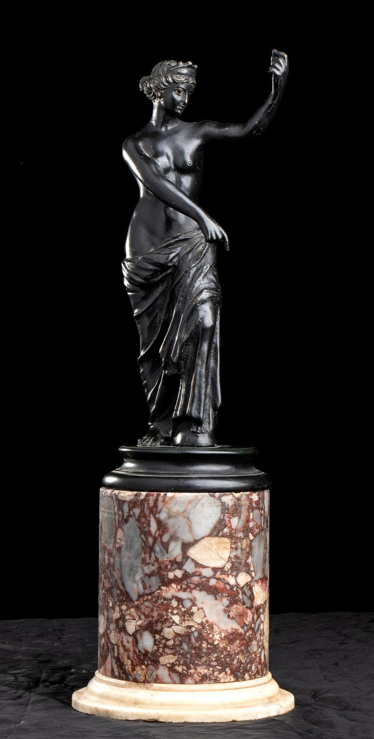 Standing on a Specimen polychrome marble base in rare and specimen marble breccia di Schio and white statuary marble, Aphrodite is depicted semi-naked, with a himation (cloak) covering her lower body supported by the knee of her slightly bent left