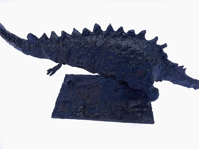 Circa 1970s brutalist steel dinosaur. This creature is an eye catcher, with its long sinuous body and roughly textured body. The metal has been coated with a tar-like finish, which makes the animal look quite prehistoric. There are hints of dark
