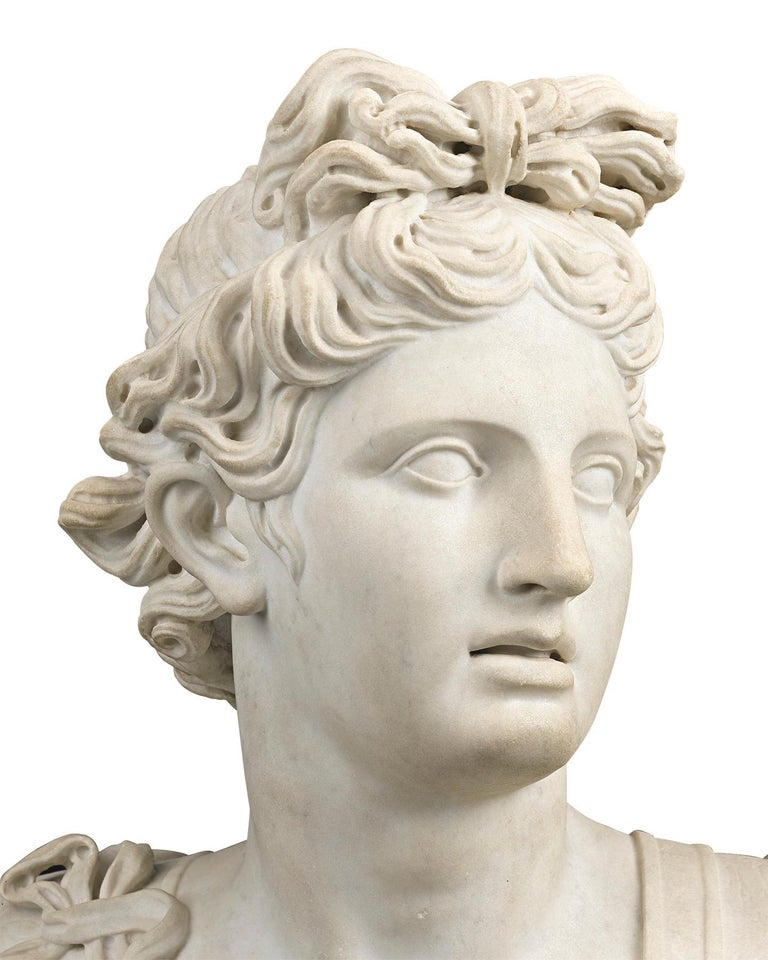 An imposing work of extraordinary artistry, this marble bust captures the visage of Apollo, the handsome god who is one of the most legendary Olympian deities from antiquity. The son of Zeus and Leto, and twin brother of the huntress Artemis, he was