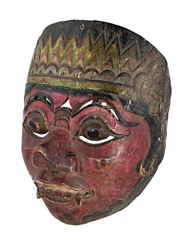 """This mask, which features a face with round eyes, fangs, and a beet red face, was created by an unknown Indonesian artist. It is approximately 7 1/2"""" high and 6"""" wide."""