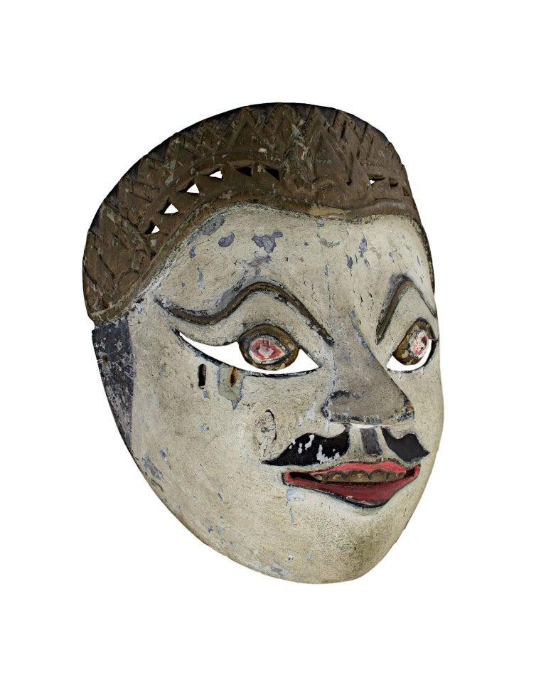This mask, created by an unknown Indonesian artist, features round eyes, a white face, and a painted mustache. It is approximately 7