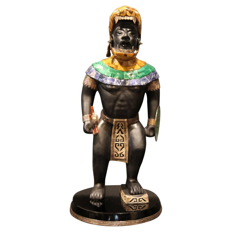 Mayan or Aztec warrior sculpture with lapis, malachite, and tiger's eye inlay. The sculpture's club is a detachable metal piece with an orange-colored precious stone. The sculpture sits on a base with a decorative metal rim.