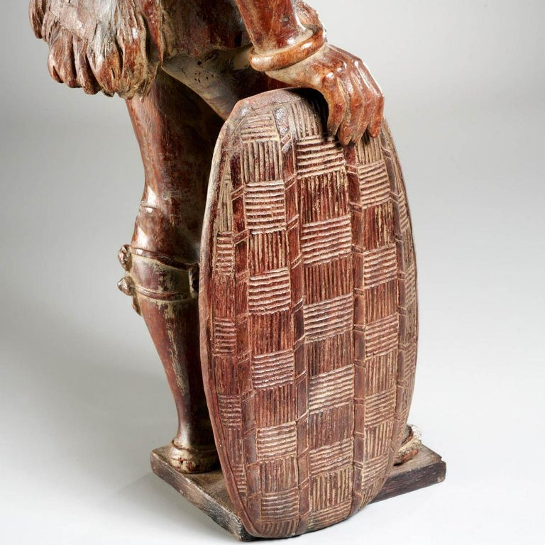 Orientalist African Hunter Leaning on His Shield Carved Wood Black Forest  Continental School, 19th century  21 inches  This is an exceptionally beautiful and exceptionally rare wood carving of an African (