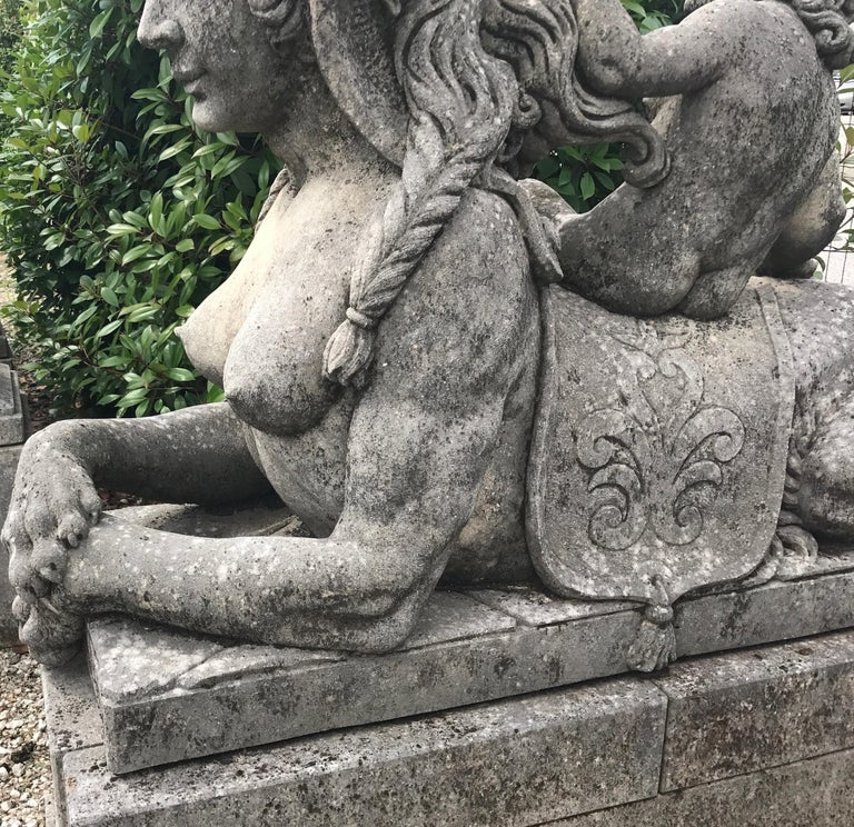 Designed as entrance guardians, this pair of mythical lady sphinx statuary display the head and chest of a neoclassical woman and the body of a recumbent lion on a rectangular stone base. Very good condition with light grey patina due to age and