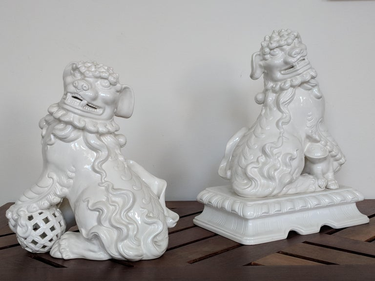 Pair of white ceramic Italian Foo Dogs that are appropriate for an important space. The expression on the dogs is beautifully detailed and may be suitable for a contemporary or antique setting. One of the dogs is slightly larger than the other;