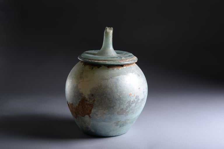 Roman glass cinerarium, dating to the 1st or 2nd century AD.  The hand-blown ovoid body with folded tubular rim, the base slightly kicked in, the separately blown lid with a thick cylindrical handle at the top and pinched in at the sides.  An