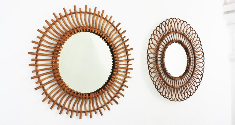 Beautiful Unmatching pair of rattan sunburst flower shaped mirrors, Spain, 1960s The set is comprised by two Mid-Century Modern round sunburst and flower shaped mirrors handcrafted with rattan, wicker and cane. They have all the taste of the