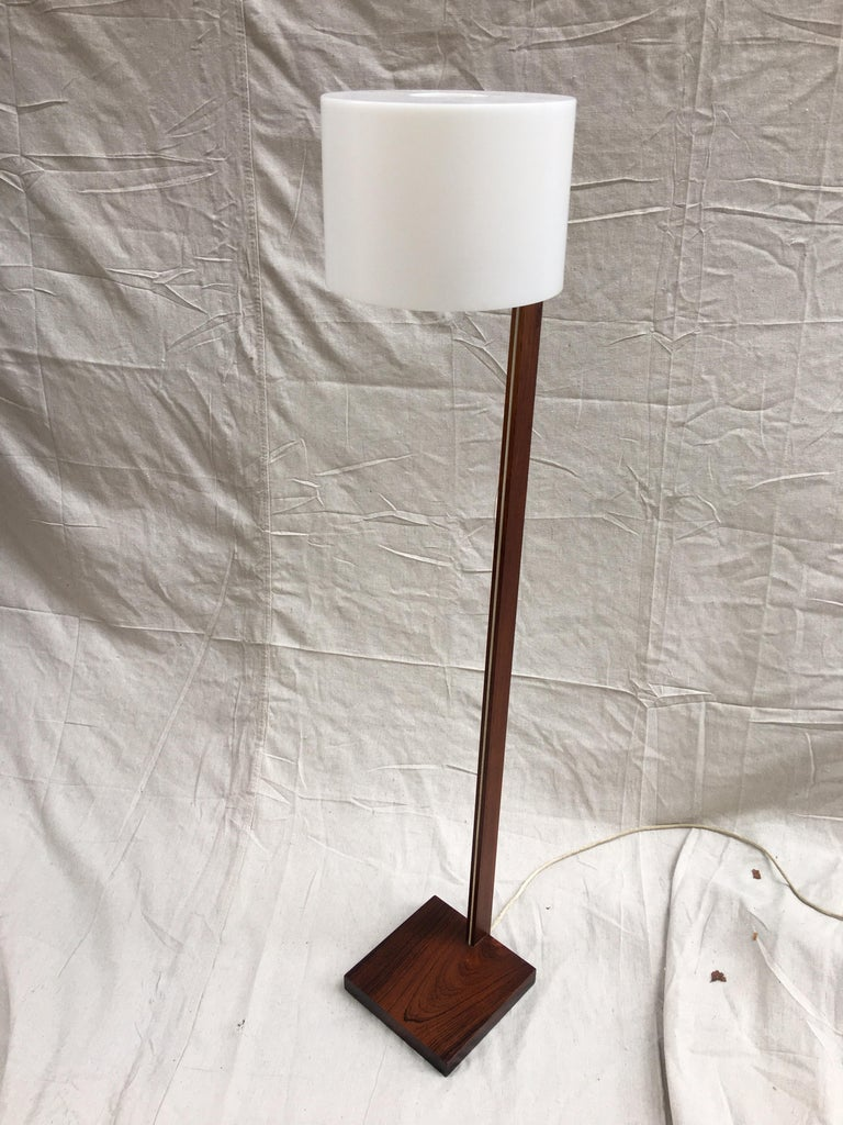 Uno and Osten Kristiansson rosewood floor lamp. Beautiful rosewood in great shape with no fading. Switch at top of rosewood. Plastic shade shows the slightest mold or crack line, see photos. Really does not show but present. Nice to find in