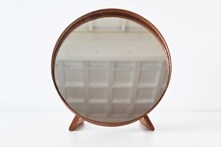 Wonderful table mirror designed by Uno and Östen Kristiansson for Luxus, Sweden 1960. The elegant simplicity of the form is nicely contrasted with the texture and richness of the teak. This mirror is very well crafted with nice dovetail connections