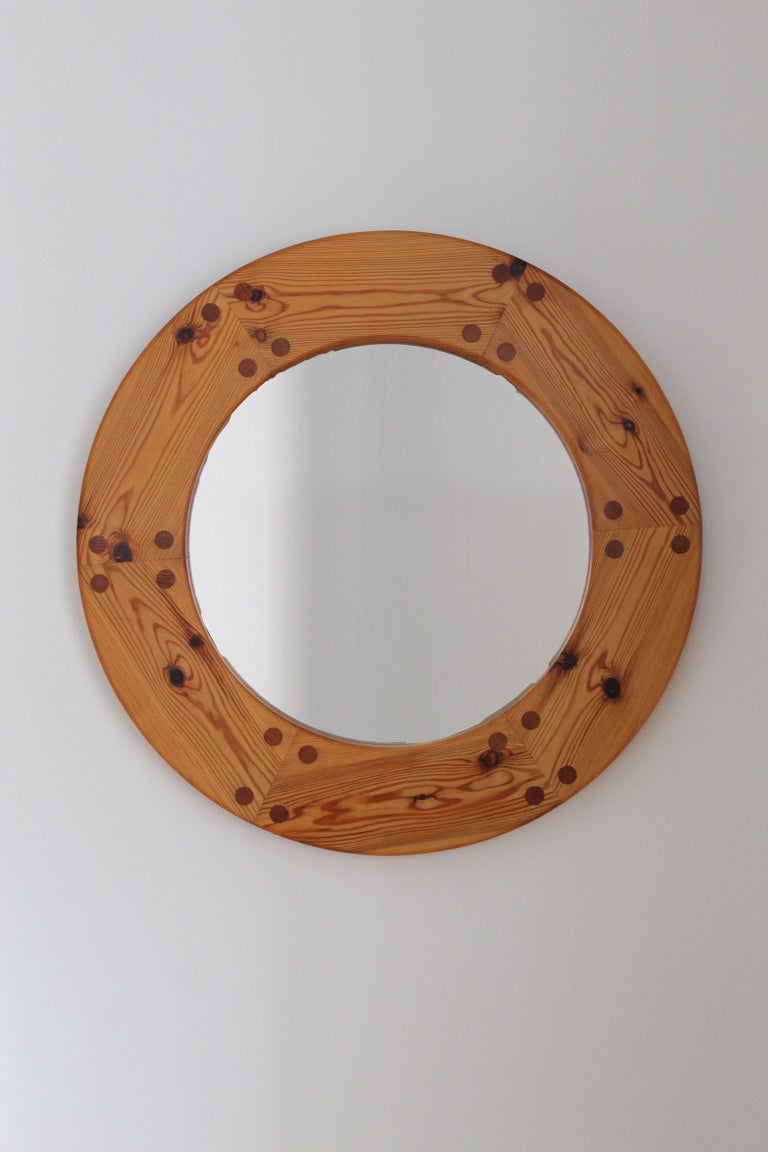 A sculptural round wall mirror. Designed by Uno Kristiansson, for Luxus, Sweden, 1960s. Features revealed teak-colored joinery.   Other designers of the period include Axel Einar Hjorth, Roland Wilhelmsson, Charlotte Perriand, Pierre Chapo, and