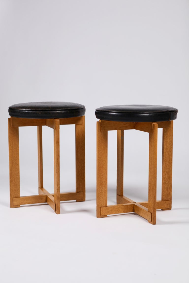 A pair of rare black leather and oak stools by Uno & Östen Kristiansson for Luxus, executed in Sweden in the 1960s. Sculptural base and padded seats, original leather (one stool with a small break in the leather), with wear and nice patina to the