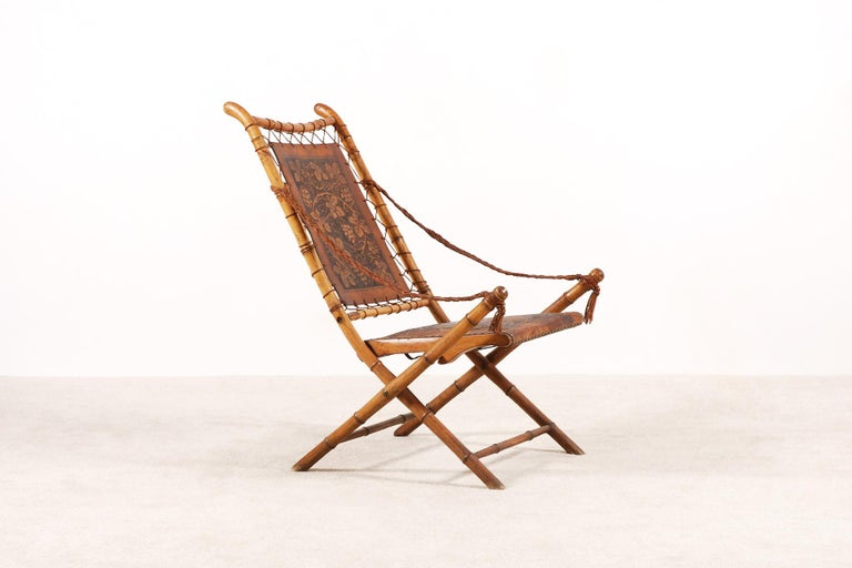 Unusual and unique folding chair, France, 19th century. Oak wood structure imitating the bamboo. And extremely Fine hand-tooled leather work. Laced leather armrests. Very decorative and ideal as a bedroom chair. Very good condition, can be used