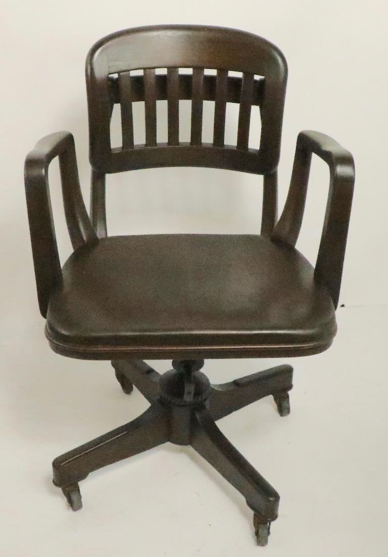 Unusual architectural swivel desk, office chair by Gunlocke. This example has a tilting backrest as well as an adjustable tilting back support and a swivel base which is mounted on wheel caster feet. The chair has been newly refinished, and is in