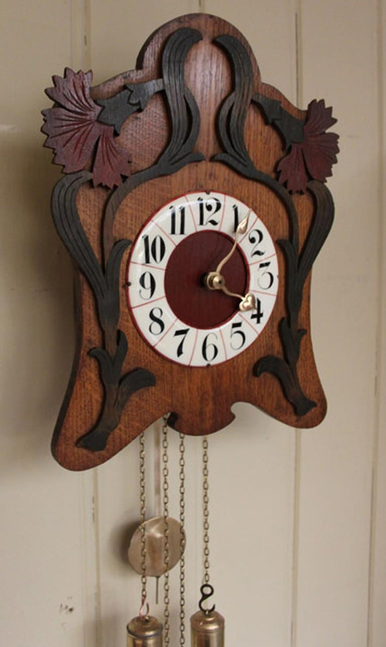 An unusual Art Nouveau wall clock from the Black Forest. It has an oak front with carved, colored applied vine leaves, and an enamel chapter ring with red lines and block numerals. It has a wooden plated movement with bass weights and pendulum that