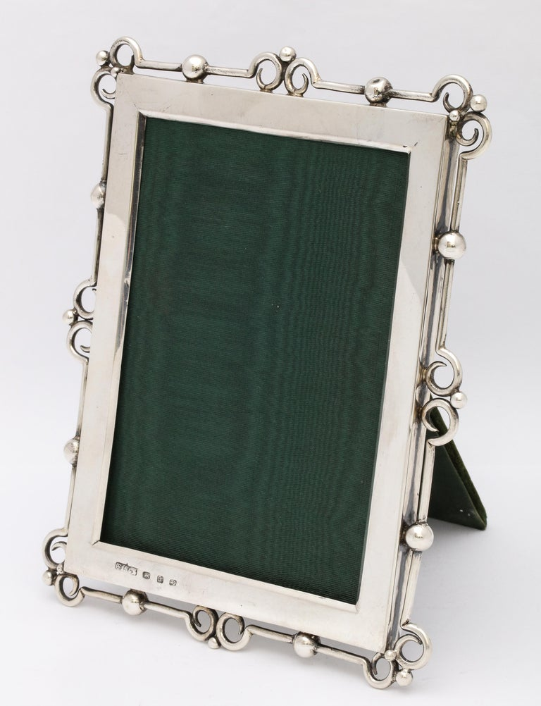 Unusual, Arts & Crafts, sterling silver picture frame, Birmingham, England, year hallmarked for 1896, E. Mander and Sons - makers. Velvet back. Measures: 7 1/4 inches high x 5 3/4 inches wide x 4 3/4 inches deep (when easel is in open position).