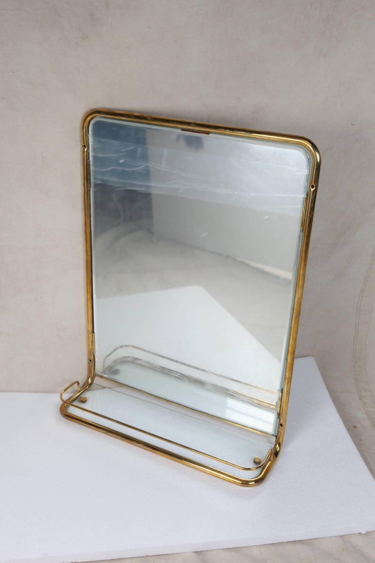 A great brass wall mirror from the stateroom of a decommissioned cruise ship. Features a new mirror and glass shelf with the original brass railing around it, circa 1960s. As of this writing I have three pieces.  Nautical antiques on nantucket