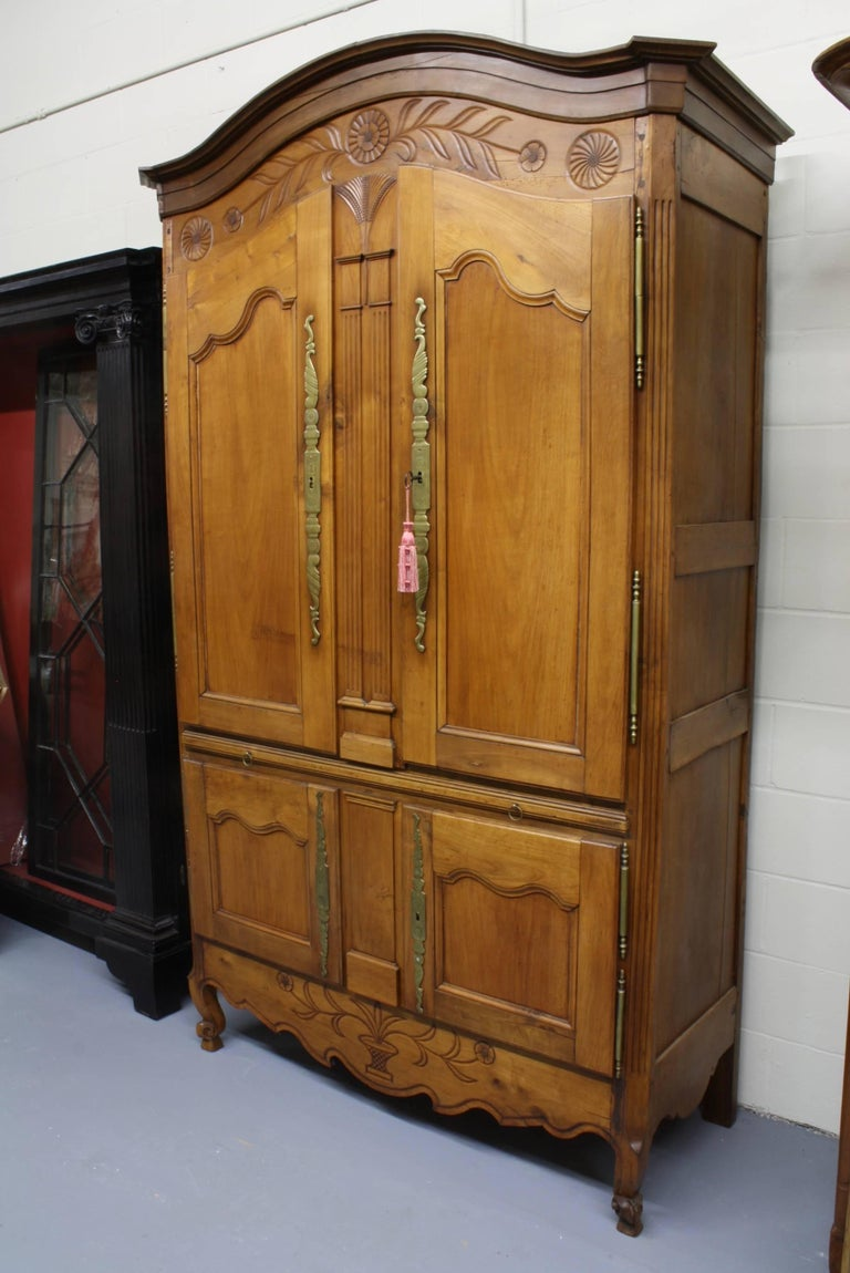 This unusual cherry cupboard or armoire from Brittany features four doors with a pull-out shelf separating the upper and lower sections. The upper sections features a pair of nicely carved columns, surmounted by a very finely carved wheat sheaf. The