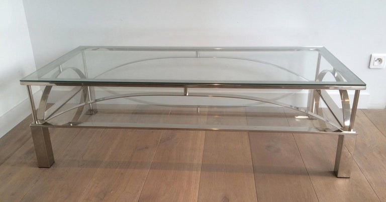 This unusual coffee table is made of chrome with 2 glass shelves. It has rounded chromed metal parts on each side of the table. This is a nice French work, circa 1960.