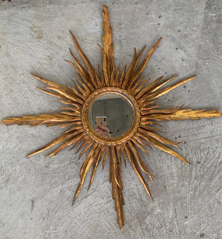 A very beautiful small sunburst mirror finely carved with 24-karat gold leaf finish. Very unusual size and interesting patina, Spain, 1930s. Measures: Glass diameter 6.5cm / overall dimensions 30 in diameter.