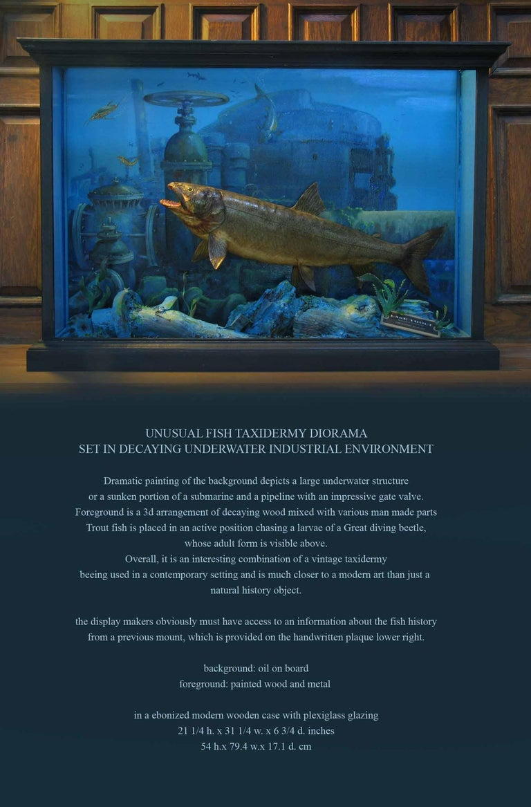 Unusual fish taxidermy diorama set in decaying underwater industrial environment.