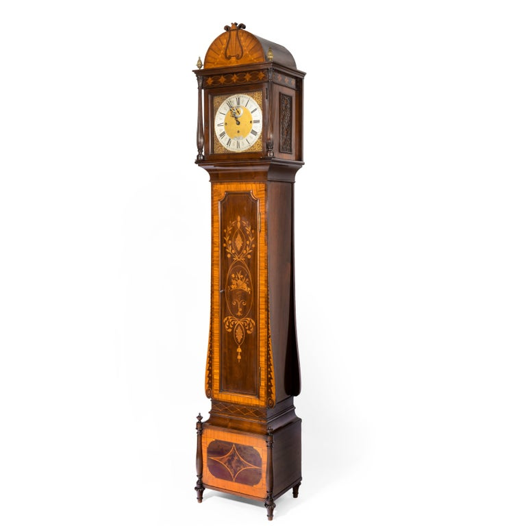 An unusual flame mahogany long-case clock attributed to Maples with a Smith & Sons 3-train movement, the case with a stepped base, the hood with two fluted columns and brass finials surmounted by a hemi-spherical crest decorated with a lyre against