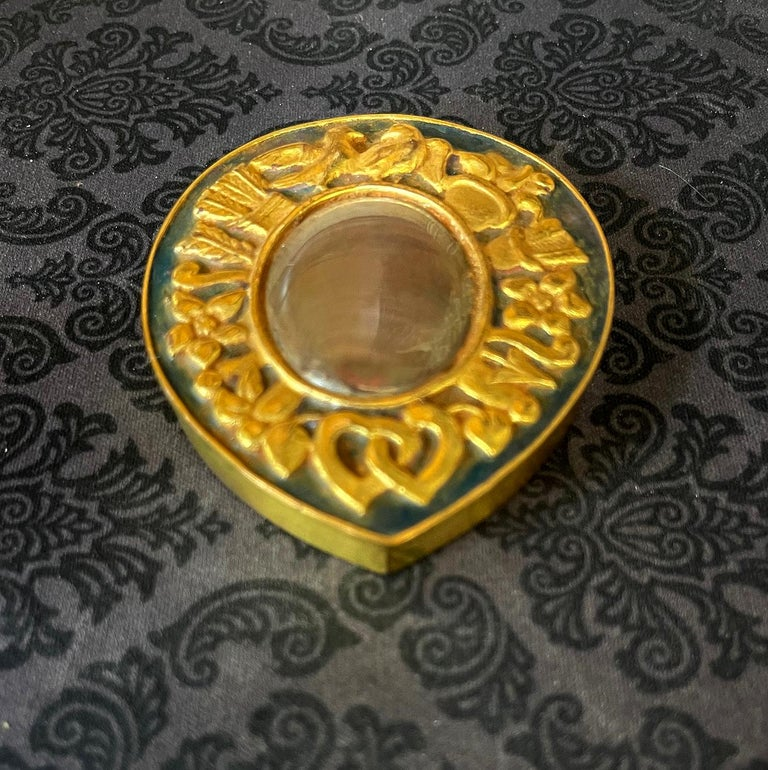 A cast bronze box used as a poudrier (powder box) by French Parisian Art Jeweler Line Vautrin (1913-1997) circa 1950s. The lidded box is in a form a tear drop and features a relief band of motif including two kissing pigeons, arrows tails and heads