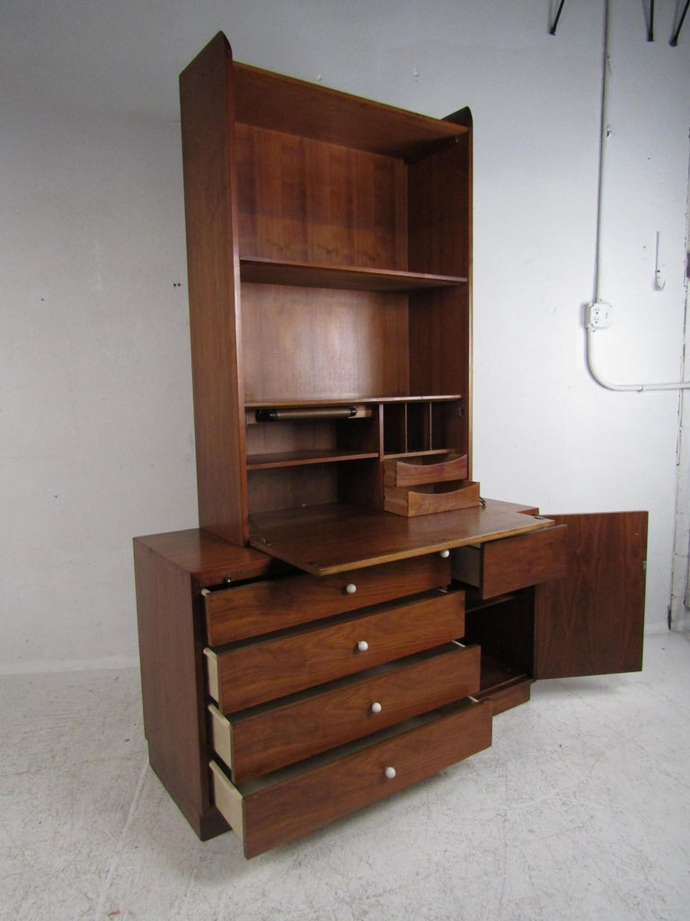 A beautiful vintage modern wall unit that consists of two pieces. A unique design that offers plenty of storage without sacrificing style. Sturdy construction, elegant walnut wood grain, and iconic round white drawer pulls show quality midcentury