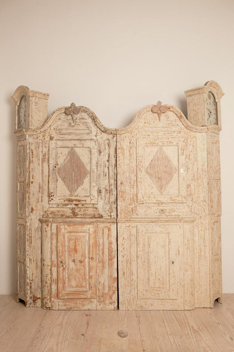 Unusual pair of Gustavian corner clock cabinets, origin: Mora, Sweden, circa 1780  Each cabinet with matching working, tall case clocks decorated with four fluted diamond patterns and upper and lower cabinet spaces. Dry-scraped to original