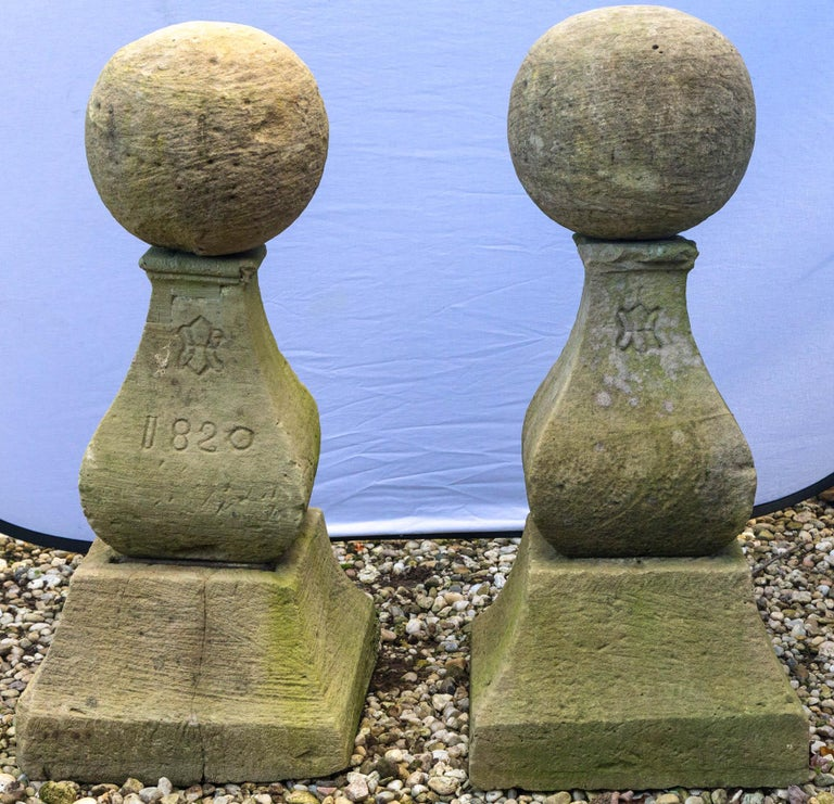 Pair of cast stone finials with ball tops and ornamented fleur-de-lys, 1820 carved in stone.