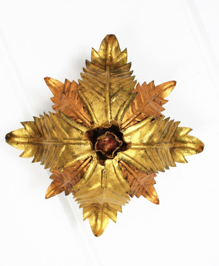 Lovely hand-hammered iron flower burst light fixture with leaves in two tones (golden and copper), a central rose with red accents and gold leaf finish. An sculptural piece that could be perfect for a courtesy bathroom, Spain, 1950s.  Available