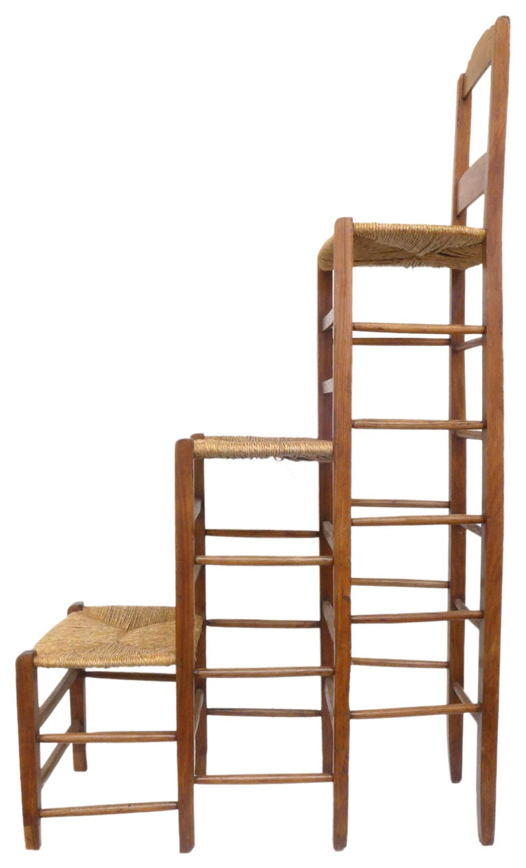 A wonderful and unusual triple-stepped wood and woven-rush chair. A curious and unexpected form; a traditional piece of Americana utilitarian decor expanded to near surrealist-sculpture proportions. Likely a playful one-off by an unknown