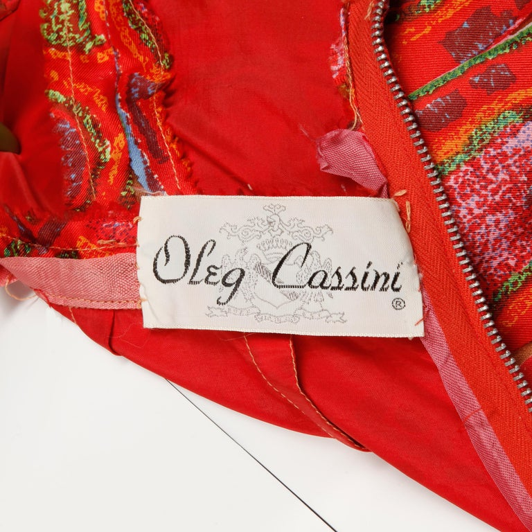 Unworn with the original tags still attached! This vintage 1960s silk cocktail dress by Oleg Cassini features sequin embellishment and an Indian-inspired print. Fully lined with rear metal zip, hook and snap closure. Fits like a modern size