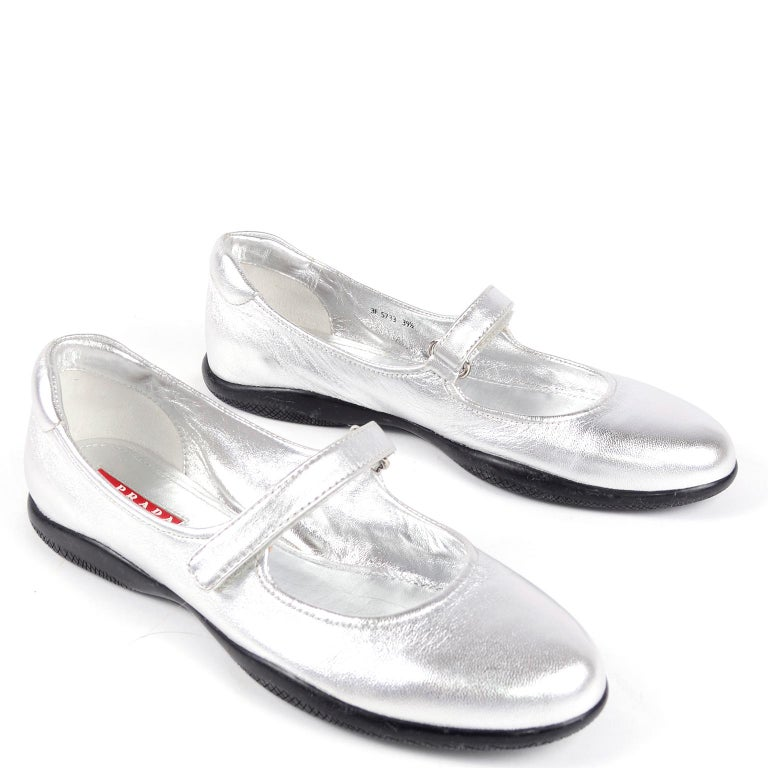 These pretty silver Prada shoes have ever been worn! These Mary Jane flats have a velcro strap, a round toe. and rubber sole. We think these can be worn casually or with holiday party dresses!  Labeled an Italian size 39.5 Measurements:  BALL: