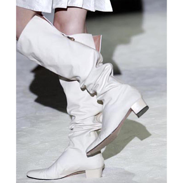 These are iconic Tom Ford for Gucci over the knee boots that we have documented from his Spring Summer 2004 runway show.  That was his last Spring show for Gucci. These unique Gucci boots are an ivory white canvas with leather lining that can fold