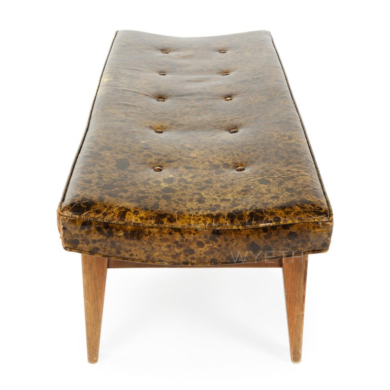A finely crafted and versatile bench having a button-tufted rectangular curved seat which retains its original 'tortoise' upholstery and floats above an architectural frame made of walnut.