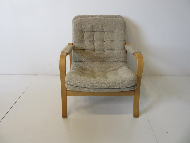 A sculptural birch wood framed lounge chair upholstered in Danish styled woven oatmeal fabric as are the arm pads with button back and seat. A simple design that mixes with any decor from any period, made in Sweden by DUX.