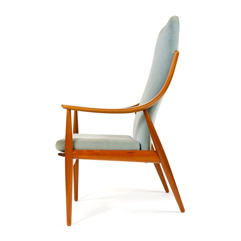 A high back armchair designed by Peter Hvidt & Orla Mölgaard-Nielsen having an exposed teak frame with expressive bent laminated curved arms and vintage blue upholstery. Made in Denmark by France and Daverkosen, circa 1950s.