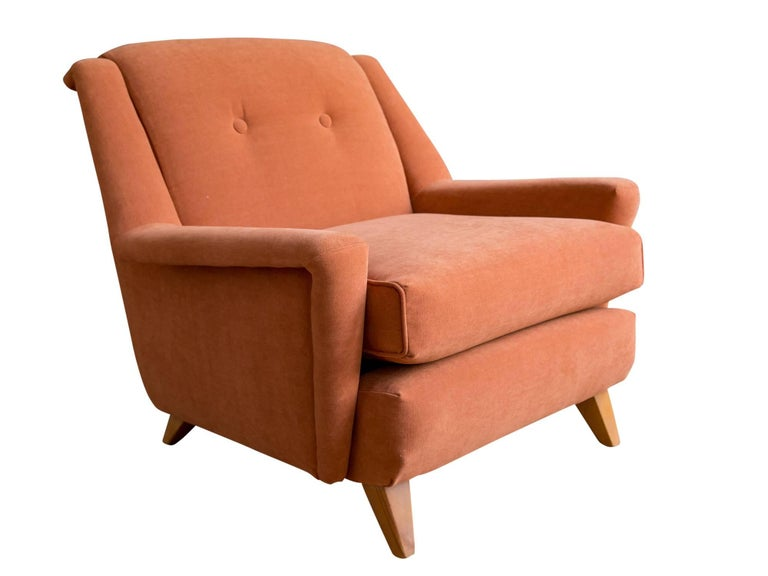 A generously sized lounge chair by Heywood Wakefield, circa 1950s. Featuring a Modernist sculptural form with wide arms and high back supported by flared maple legs. Recently upholstered in a terracotta cotton chenille.   A comfortable reading