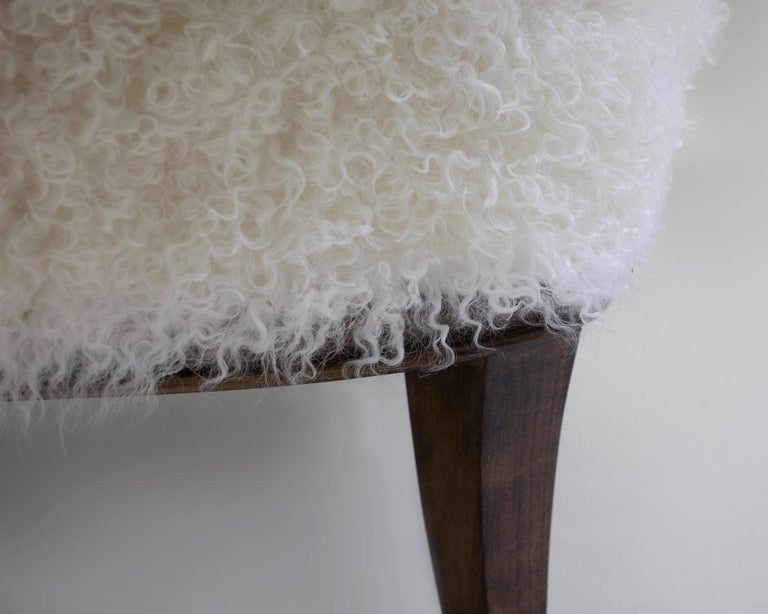 The Willow ottoman created to match the club chair of same name is shown in matching off white faux skin on wood stained legs. Hand carved and upholstered with feather and down seat cushion with metal leg caps. Made custom to your specifications as