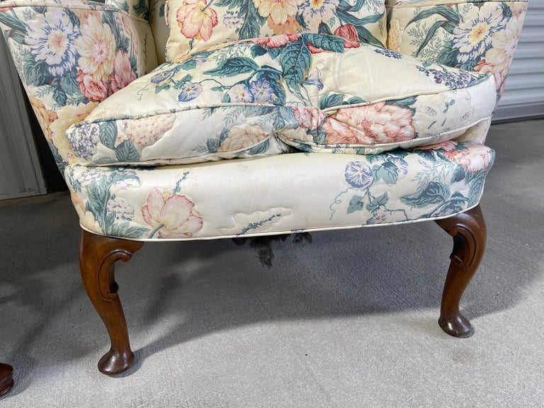 Upholstered Queen Anne style wingback chair with pad feet, 20th century. Throw pillow included.