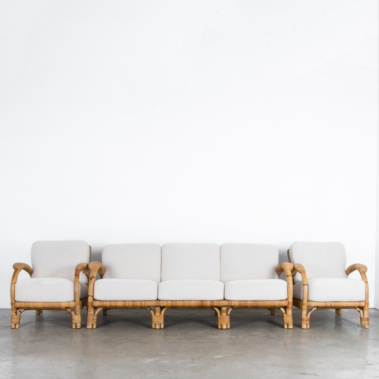 "A three piece sofa set from circa 1970, produced by German manufacturer ""Arco."" This vintage piece has a great modern vibe, subtly aged with the colors and textures of nature. The warm brown rattan is crafted with the highest quality, and updated in"